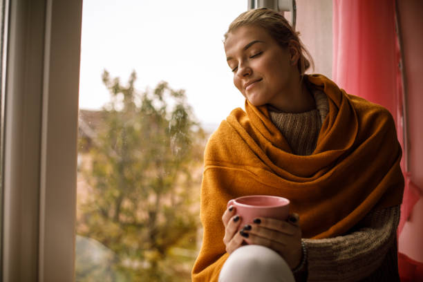 Smiling young woman enjoying a warm cup of tea on a cold autumn day stock photo