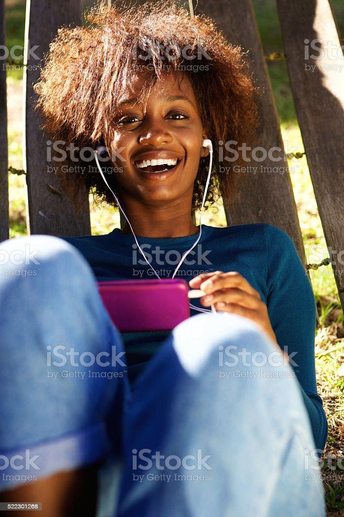 Smiling young woman enjoying music on smart phone stock photo