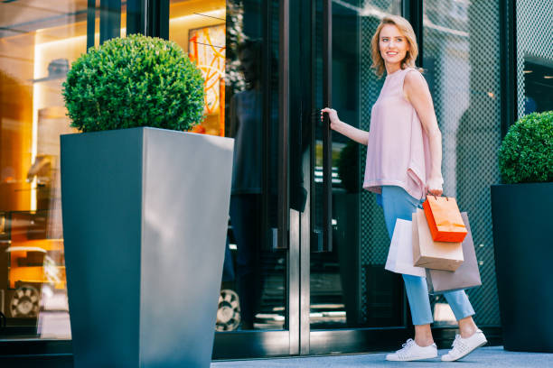 Smiling young woman entering the shop and holding bags stock photo