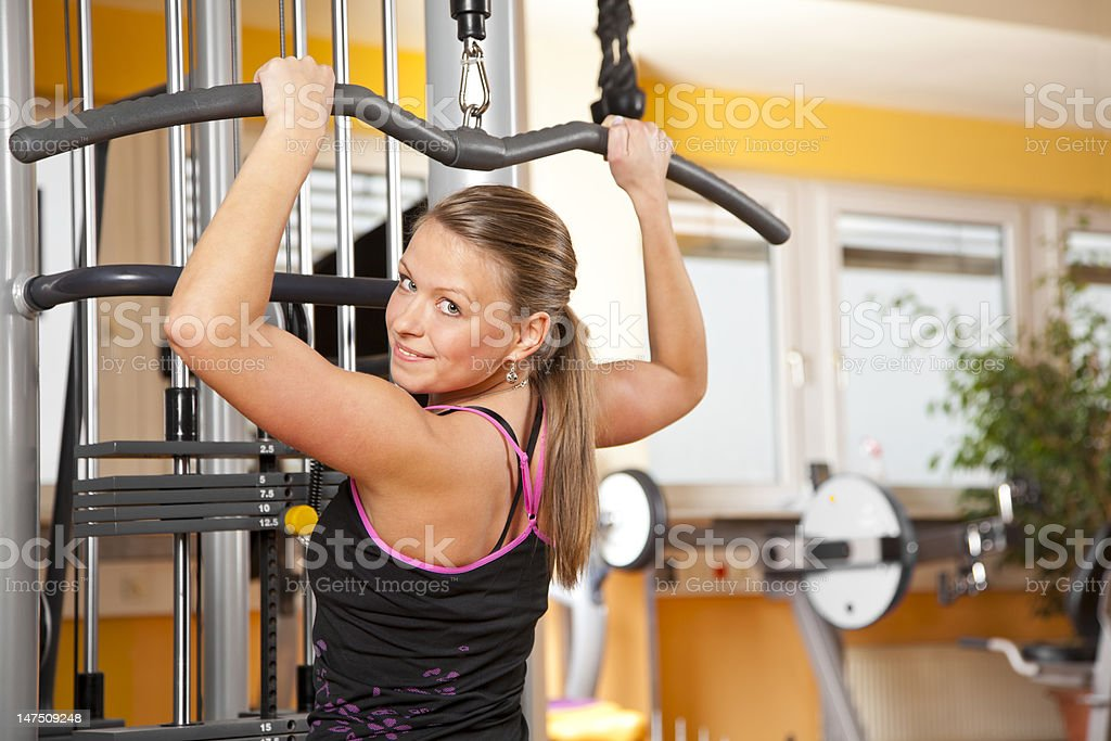 smiling young woman exercising latissimus dorsi in gym royalty-free stock photo