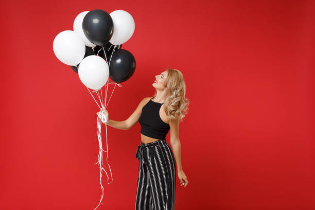 Smiling young woman girl in black clothes posing isolated on red wall background. St. Valentine's Day birthday holiday party concept. Mock up copy space. Celebrating hold air balloons looking aside. stock photo