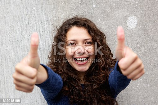 istock Smiling young woman giving thumbs ups 615918198