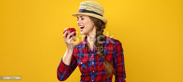istock smiling young woman grower on yellow background eating an apple 1036177394