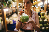 Authentic Thai street food in Bangkok. Young woman is having a refreshment with delicious coconut water on a hot summertime evening.