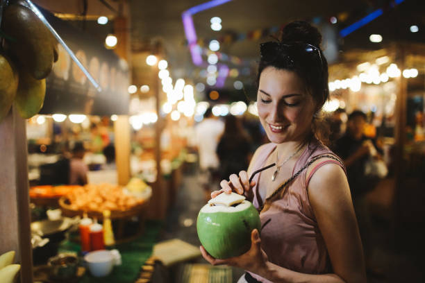 Smiling young woman having a delicious and fresh coconut water on the go Authentic Thai street food in Bangkok. Young woman is having a refreshment with delicious coconut water on a hot summertime evening. night market stock pictures, royalty-free photos & images