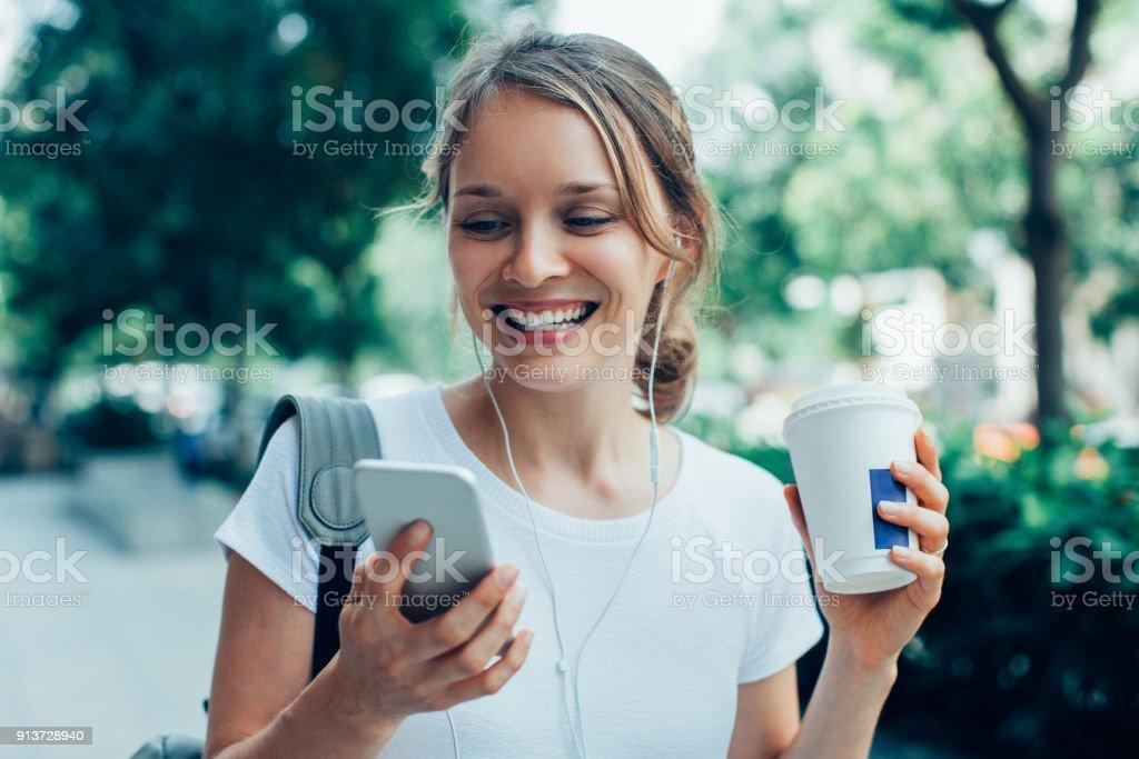 영상 통화를 야외에서 데 웃는 젊은 여자 - 로열티 프리 T 셔츠 스톡 사진
