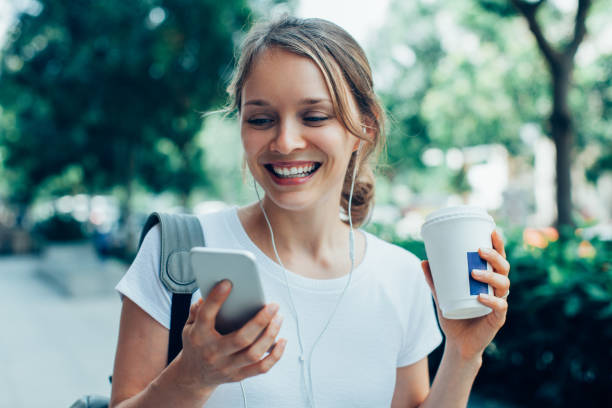 Smiling Young Woman Having Video Call Outdoors Closeup portrait of smiling young beautiful woman walking, holding drink, wearing headphones and having video call on smartphone on street on the move stock pictures, royalty-free photos & images
