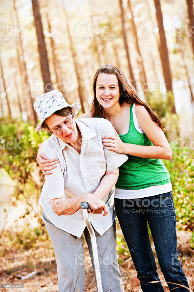 Smiling young woman helps bent old lady to walk royalty-free stock photo