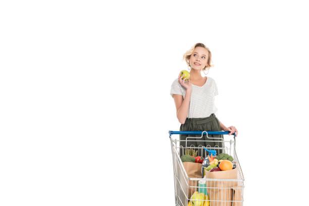 lächelnde junge frau hält apfel und auf der suche - trolley kaufen stock-fotos und bilder