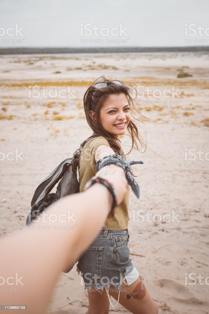 Smiling young woman holding friend's hand Portrait of smiling young woman holding friend's hand on sand. Female hikers are enjoying at desert. They are spending summer vacation together. 20-24 Years Stock Photo