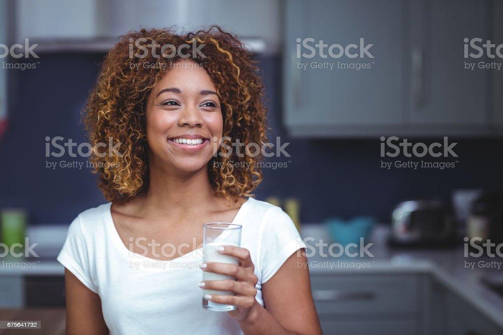 Sonriente joven mujer sosteniendo el vaso de leche - foto de stock