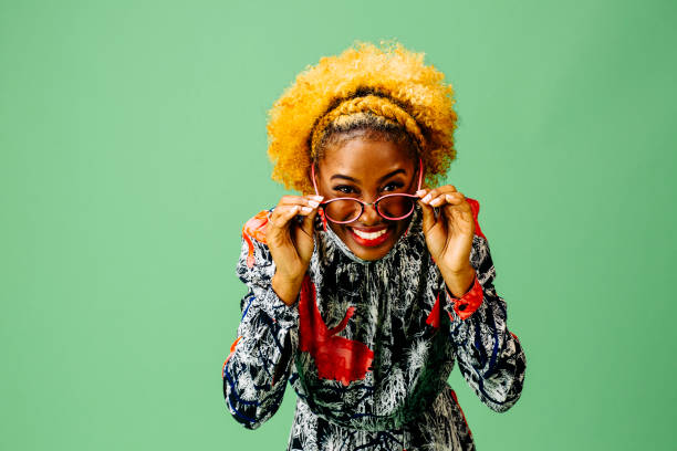 Smiling young woman  holding her glasses Smiling young woman  holding her glasses, isolated on green studio background nerd hairstyles for girls stock pictures, royalty-free photos & images