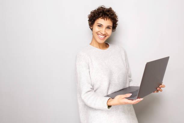 lächelnde junge Frau hält Laptop-Computer durch weißen Hintergrund – Foto