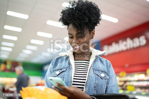1184048369 istock photo Smiling young woman holding product in supermarket and searching on the phone 1183957026