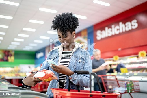 1184048369 istock photo Smiling young woman holding product in supermarket and searching on the phone 1184048678