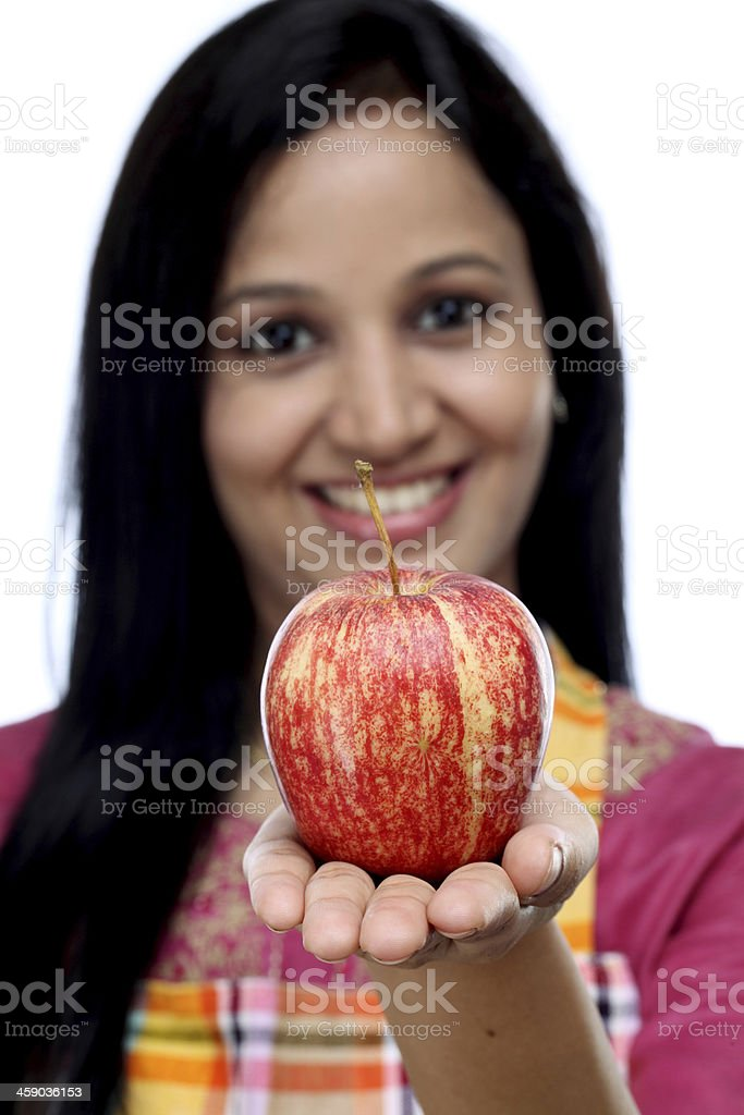 Smiling young woman holding red apple stock photo