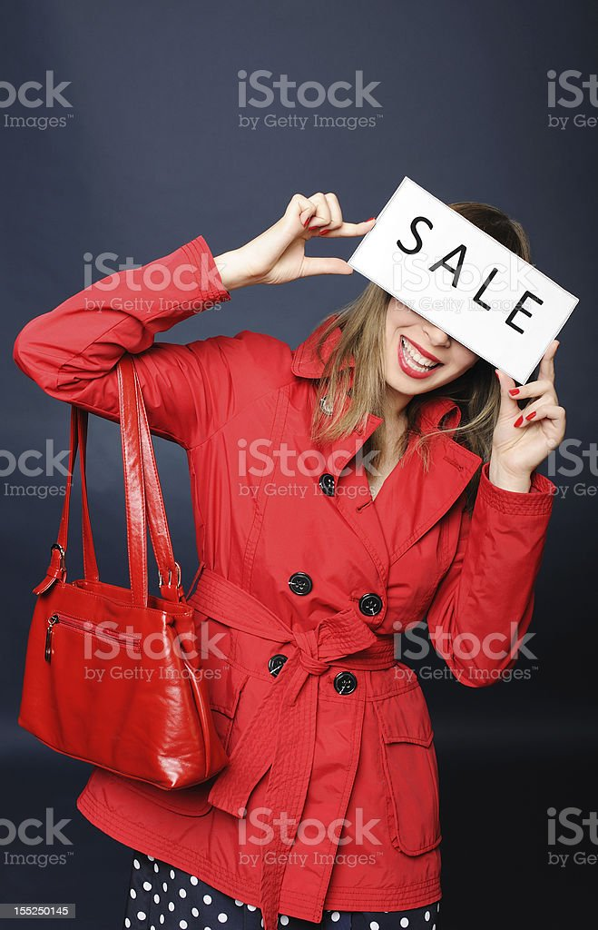 Smiling young woman holding sale sign stock photo