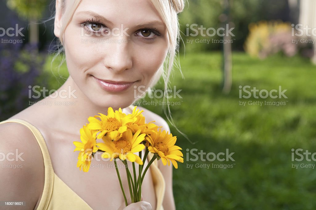 Smiling young woman holding yellow daisies stock photo