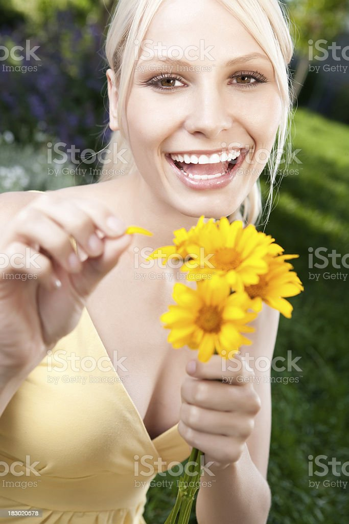 Smiling young woman holding yellow daisies royalty-free stock photo
