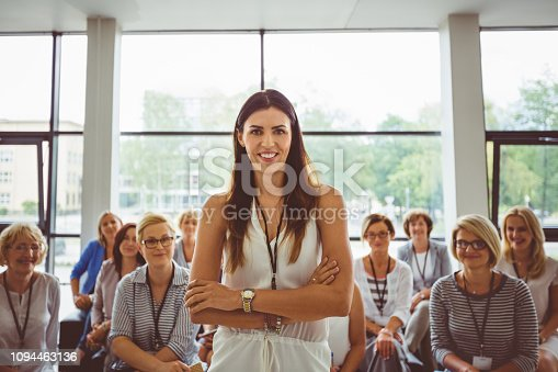 854811490istockphoto Smiling young woman in a business seminar 1094463136