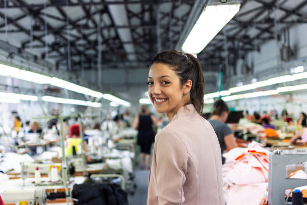 Smiling young woman in a factory stock photo
