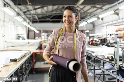 istock Smiling young woman in a fashion factory 1083251186
