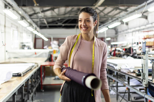 Smiling young woman in a fashion factory Smiling young woman working in a fashion factory design professional stock pictures, royalty-free photos & images