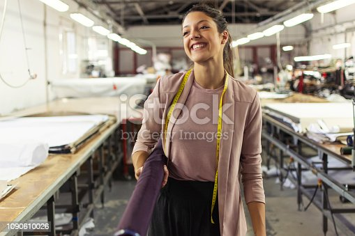 1083251186istockphoto Smiling young woman in a fashion factory 1090610026