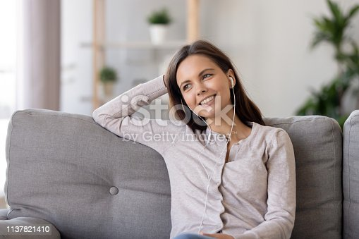 Smiling young woman in earphones, listening to favorite song, sitting on comfortable sofa at home, dreamy girl looking in distance, thinking about future, planning, enjoying music