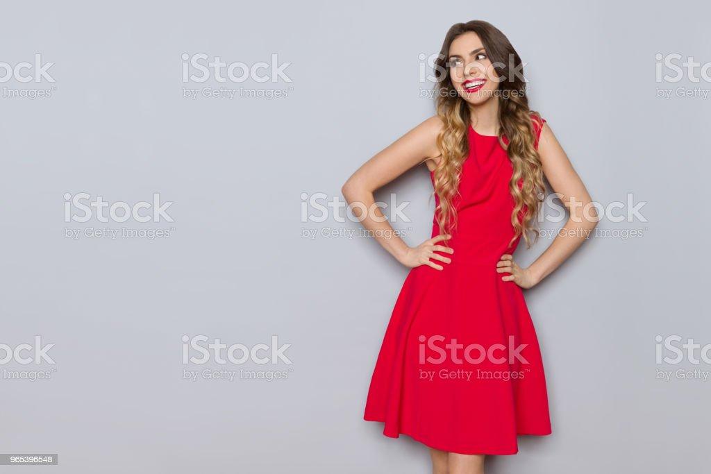 Souriante jeune femme en robe rouge élégante est à la recherche. - Photo de A la mode libre de droits
