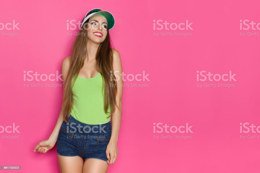 Smiling Young Woman In Green Tank Top Is Looking Away stock photo