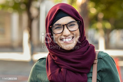 Beautiful young muslim woman wearing hijab and spectacles. Islamic curvy woman looking at camera. Closeup face of arabic girl wearing eyeglasses and looking at camera with a big grin.