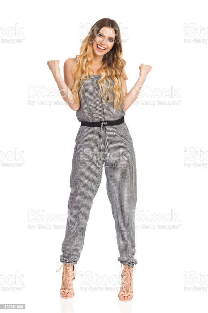 Smiling Young Woman In Jumpsuit And High Heels Clenches His Fists stock photo