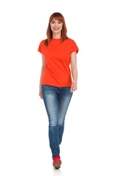 sorridente giovane donna in camicia arancione, jeans e scarpe da ginnastica rosse sta camminando verso la macchina fotografica - near foto e immagini stock