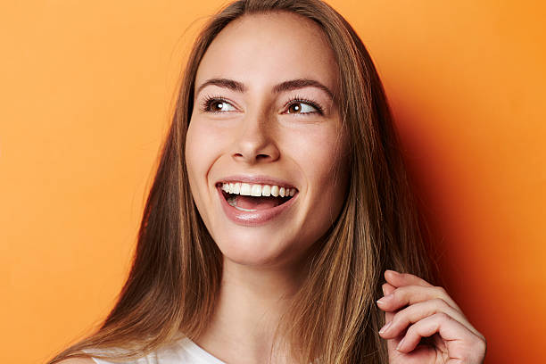 Smiling young woman in orange studio stock photo
