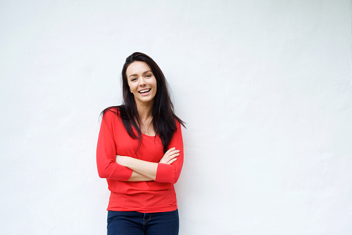 Smiling young woman in red shirt smiling against white background