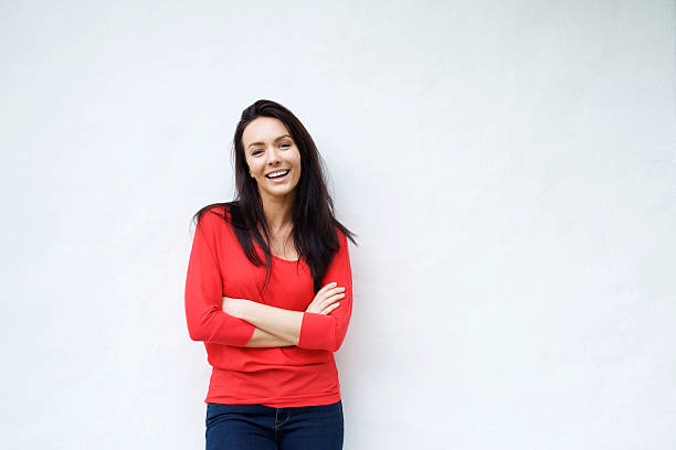 Smiling young woman in red shirt smiling against white background Portrait of a smiling young woman in red shirt smiling against white background red shirt stock pictures, royalty-free photos & images