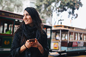 Young woman walking in downtown San Francisco, California. She is wearing casual clothing, sightseeing the old and beautiful San Francisco downtown area, texting on the smart phone.