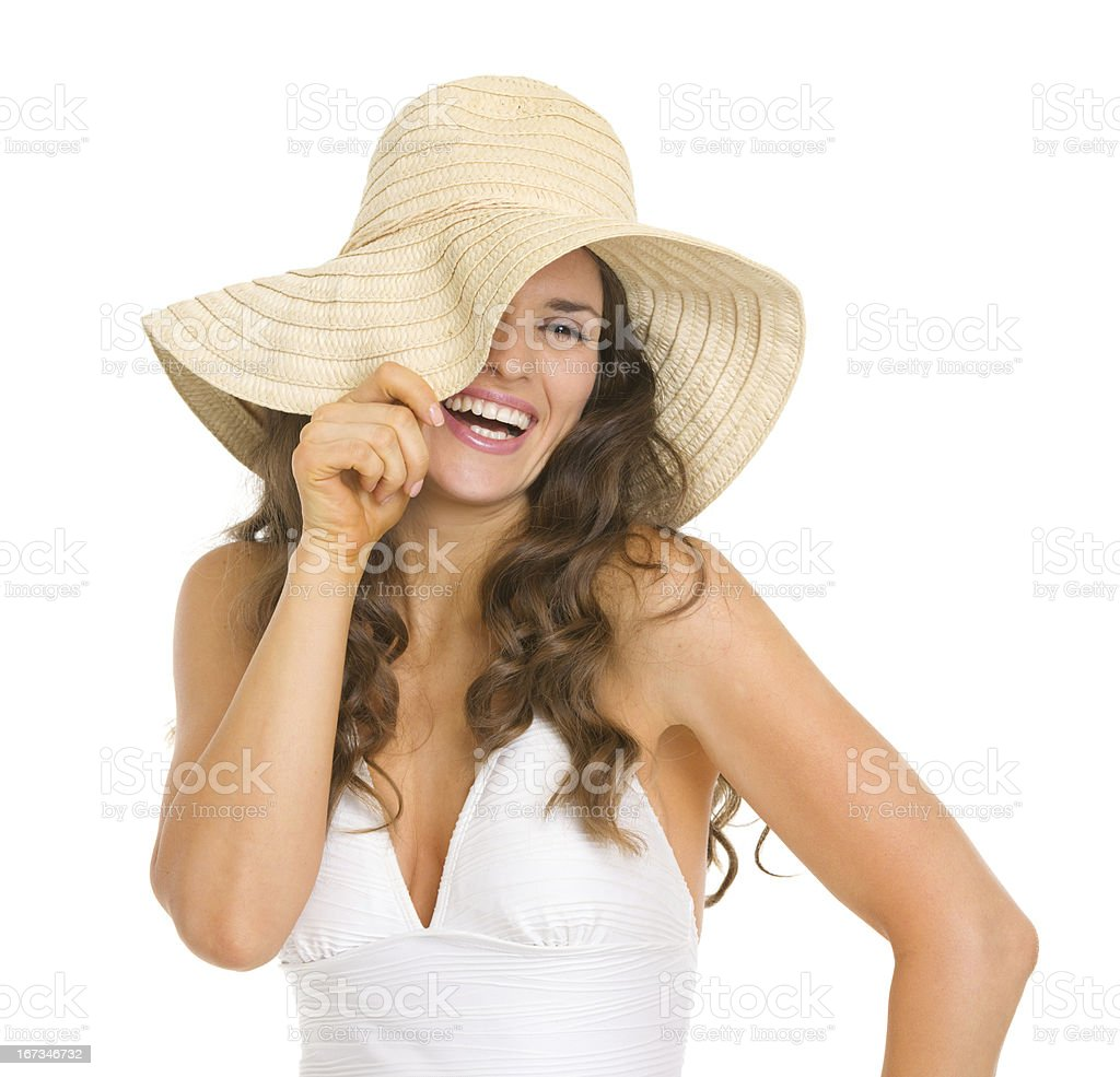 Smiling young woman in swimsuit playing with hat royalty-free stock photo