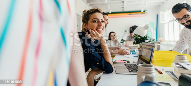 Portrait of a smiling young woman in her office, with a colleagues working next to her // wide photo dimensions