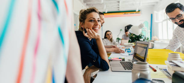 Smiling young woman in the office Portrait of a smiling young woman in her office, with a colleagues working next to her // wide photo dimensions cool attitude stock pictures, royalty-free photos & images