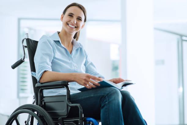 tekerlekli sandalyede gülümseyen genç kadın - tekerlekli sandalye stok fotoğraflar ve resimler