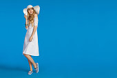 Beautiful young woman in white summer dress, striped sneakers and sun hat is looking away and smiling. Full length studio shot on blue background.
