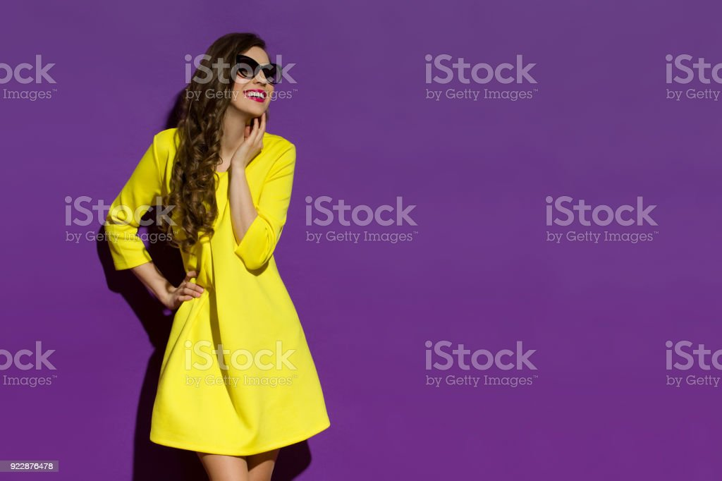 Smiling Young Woman In Yellow Dress And Sunglasses Is Looking Away stock photo