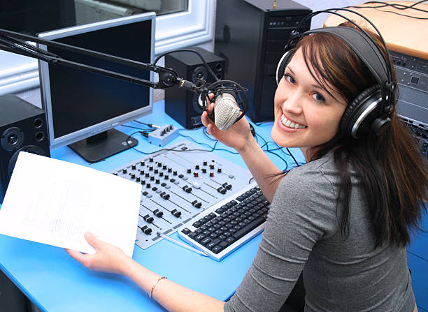 Smiling young woman inside radio cabin holding microphone Radio DJ in the broadcasting studio radio dj stock pictures, royalty-free photos & images