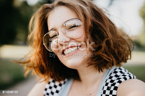 istock Smiling young woman is taking a selfie 814346132