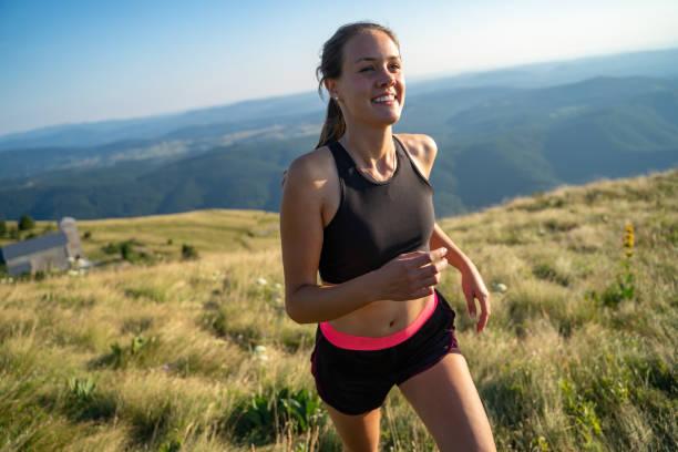 leende ung kvinna jogging på toppen av en kulle - jogging hill bildbanksfoton och bilder