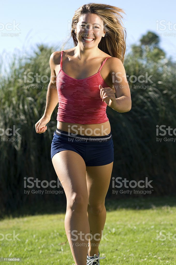 Smiling Young Woman Jogging Toward Camera royalty-free stock photo