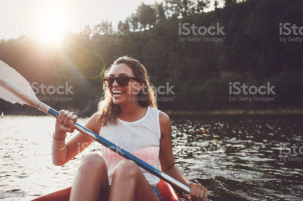 Smiling young woman kayaking on a lake stock photo