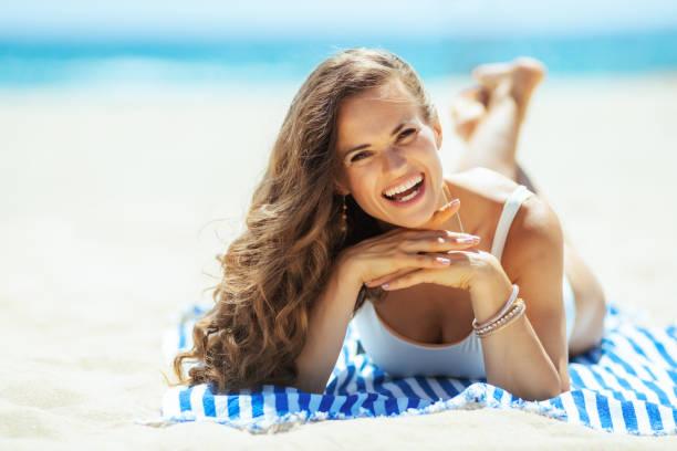 lächelnde junge Frau Handauflegen gestreiften Handtuch am Ufer des Meeres – Foto